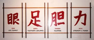 """I just took a photograph of these four 3 foot high kanji characters, painted by Norman Steenholdt. They hang in our karate museum and are chapters in the green book """"Karate of Okinawa Building Warrior Spirit"""" by Robert Scaglione The perfect photo to finish the four part series on Ansei Ueshiro. Arigato, SenseiJudy@aol.com"""